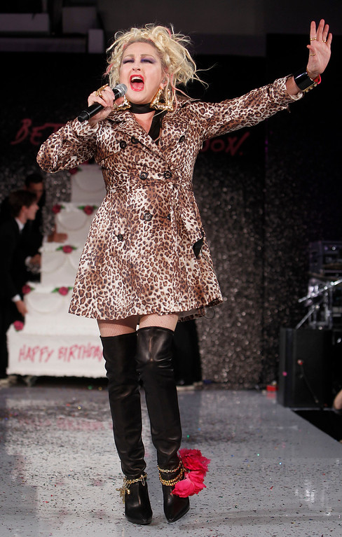 . Singer Cyndi Lauper leads a birthday cake for designer Betsey Johnson onto the runway after the Betsey Johnson Spring 2013 collection show during Fashion Week, Tuesday, Sept. 11, 2012, in New York. (AP Photo/Jason DeCrow)