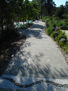 inlaid pebble snake motif in concrete path with boulder edging