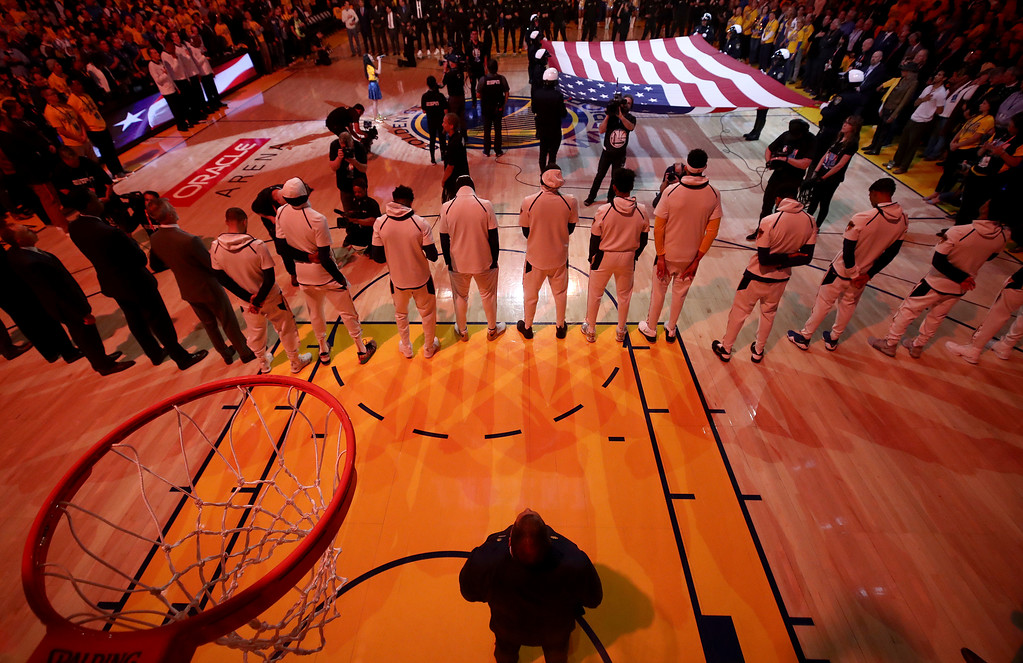 . Players listen to the national anthem before Game 1 of basketball\'s NBA Finals between the Golden State Warriors and the Cleveland Cavaliers in Oakland, Calif., Thursday, May 31, 2018. (Ezra Shaw/Pool Photo via AP)