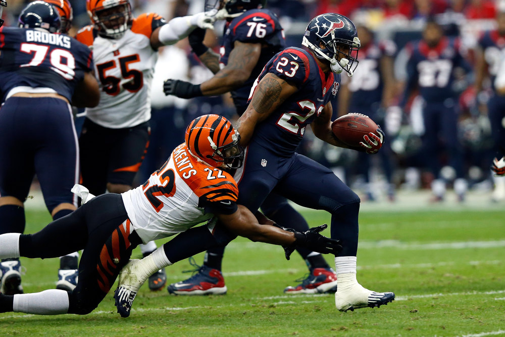 Description of . Arian Foster #23 of the Houston Texans runs the ball in the first half against Nate Clements #22 of the Cincinnati Bengals during their AFC Wild Card Playoff Game at Reliant Stadium on January 5, 2013 in Houston, Texas.  (Photo by Scott Halleran/Getty Images)