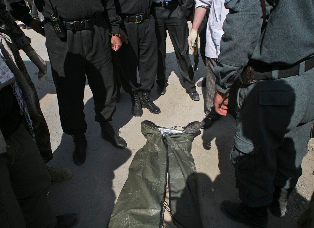 . Afghan Police officers stand around a dead body after U.S. forces shot on an Afghan truck, killing two passengers and injuring another on the road between Kabul and Bagram, Afghanistan, Monday, March 11, 2013.  (AP Photo/Ali Hamed Haghdoust)