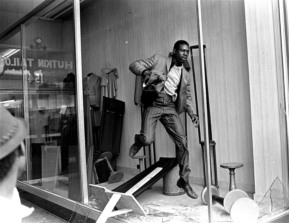 . A looter jumps over merchandise in a Memphis, Tenn. store with a handful of clothing, March 28, 1968.  Violence erupted when part of a civil rights march led by Dr. Martin Luther King, Jr. broke away from the march and began breaking into stores and pelting police officers.  (AP Photo/Jack Thornell)