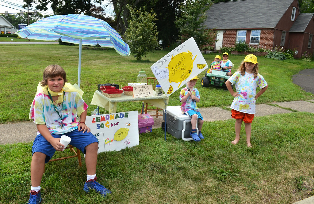 . Sporting tie-dyed shirts and yellow hats, young members of the neighboring Whiting and Wilson families wait for customers at their lemonade stand on Greenwood Road in Lansdale.   From left, Josh Wilson,  Griffin Whiting, Violet Whiting, Elisha Wilson, and Ella Whiting.   The youngsters combined the first letters of their last names to call the stand  \'W&W Lemonade\'  cookies and brownis.   They are earning money for their upcoming trip to Wildwood, New Jersey.     Monday, July 21, 2014.    Photo by  Geoff Patton