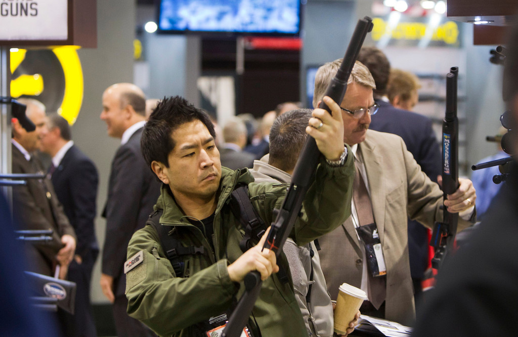 . Paul Hwang of Auburn, Washington, looks over a Mossberg shotgun during the annual SHOT (Shooting, Hunting, Outdoor Trade) Show in Las Vegas January 15, 2013. Gun dealers at the show are reporting booming sales resulting from worries about possible gun control legislation. REUTERS/Las Vegas Sun/Steve Marcus