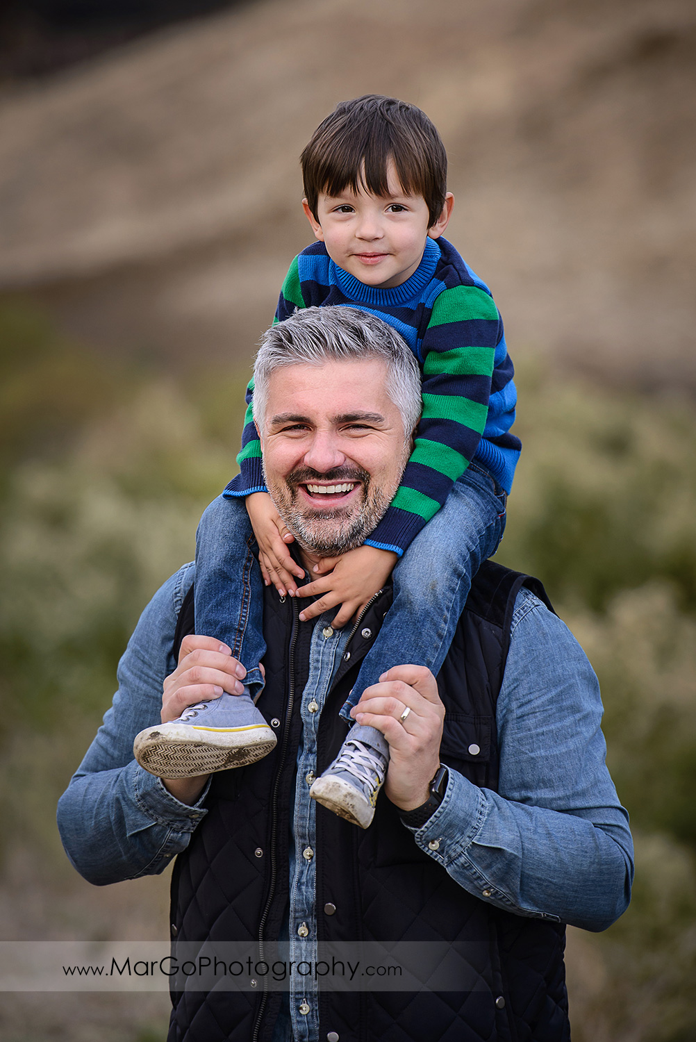 3/4 vertical portrait of father holding a boy on a piggyback, wearing in blue, green and grey clothes looking into camera during family session at Diablo Foothills Regional Park in Walnut Creek