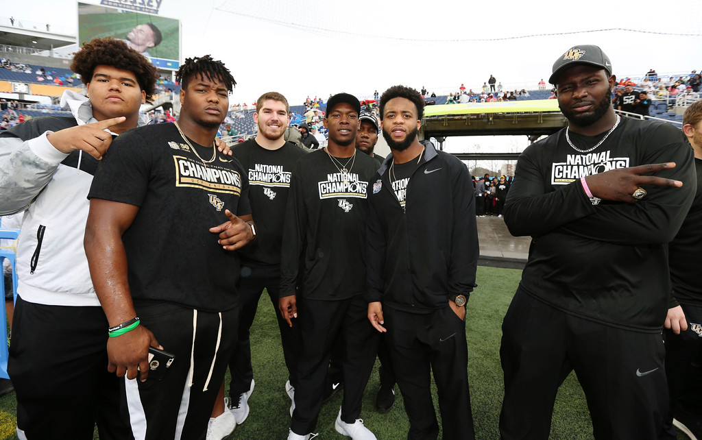 . The UCF football team poses for a photo on the sideline prior to the NFL Pro Bowl football game at Camping World Stadium, Sunday, Jan. 28, 2018, in Orlando, Fla. (AP Photo/Doug Benc)
