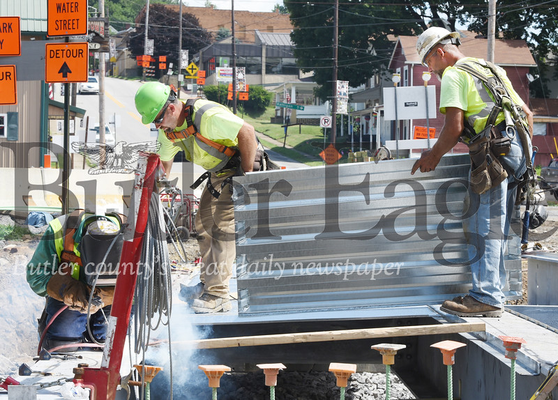 Harold Aughton/Butler Eagle: Workers from Gregory Construction in Saxonburg put the decking on the new bridge in Chicora, Tuesday, July 28, 2020.