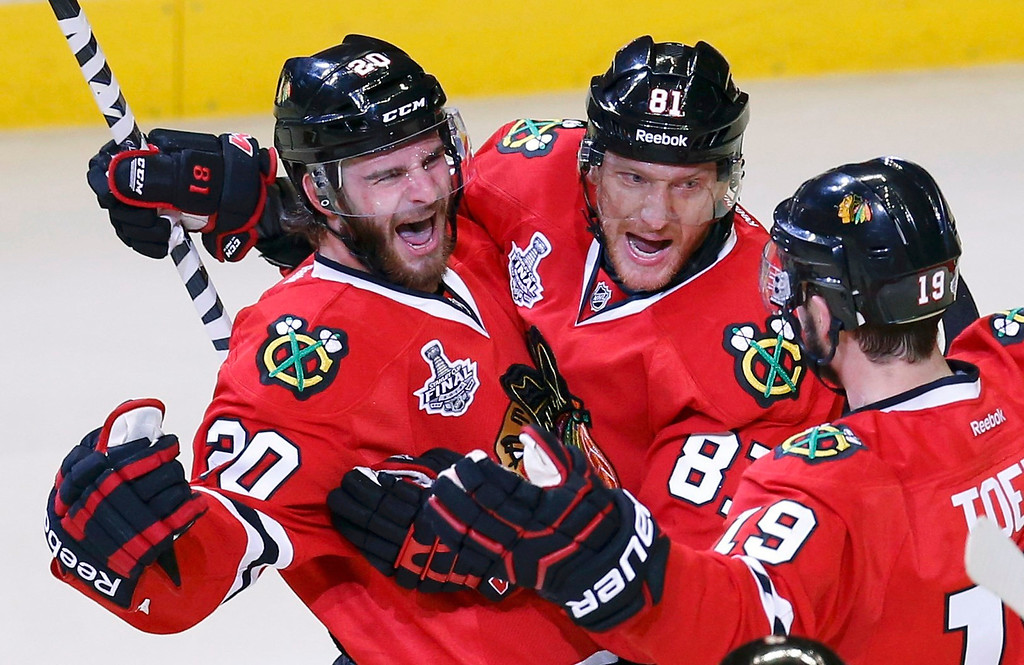 . Chicago Blackhawks\' Brandon Saad (L) celebrates his goal on the Boston Bruins with teammates Marian Hossa (81) and Jonathan Toews (19) during the second period in Game 1 of their NHL Stanley Cup Finals hockey game in Chicago, Illinois, June 12, 2013.  REUTERS/Jim Young