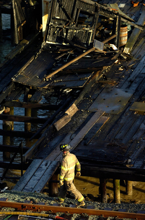 . Firefighters from the Crockett Carquinez Fire Protection District finish up at the site of a pier fire in Crockett, Calif. on Tuesday, Jan. 15, 2013. The cause of the fire on the privately owned pier, which broke out in the early morning hours, is being described as suspicious. (Kristopher Skinner/Staff)