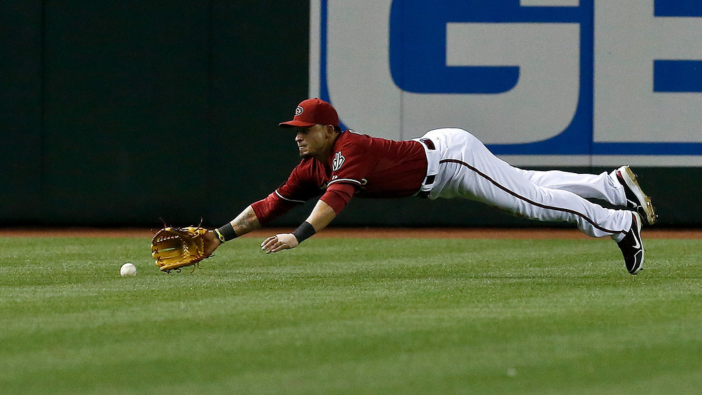 . Arizona Diamondbacks\' Gerardo Parra dives in vain for a ball hit by Colorado Rockies\' Yorvit Torrealba during the seventh inning of a baseball game, on Sunday, April 28, 2013, in Phoenix.  The Diamondbacks defeated the Rockies 4-2. (AP Photo/Ross D. Franklin)