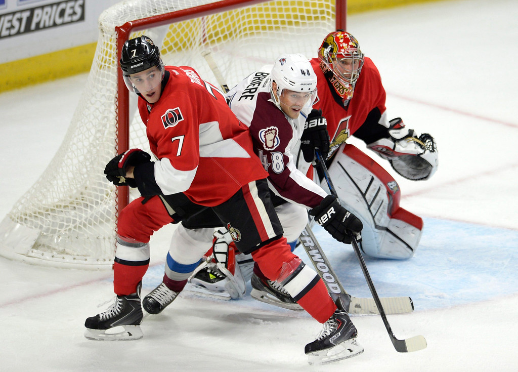 . Ottawa Senators\' Kyle Turris (7) battles Colorado Avalanche\'s Daniel Briere as Senators goaltender Craig Anderson watches for the puck during the second period of an NHL hockey game Thursday, Oct. 16, 2014, in Ottawa, Ontario. (AP Photo/The Canadian Press, Justin Tang)