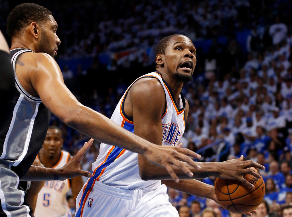 . Oklahoma City Thunder forward Kevin Durant, right, drives past San Antonio Spurs forward Tim Duncan in the first quarter of Game 4 of the Western Conference finals NBA basketball playoff series in Oklahoma City, Tuesday, May 27, 2014. (AP Photo/Sue Ogrocki)