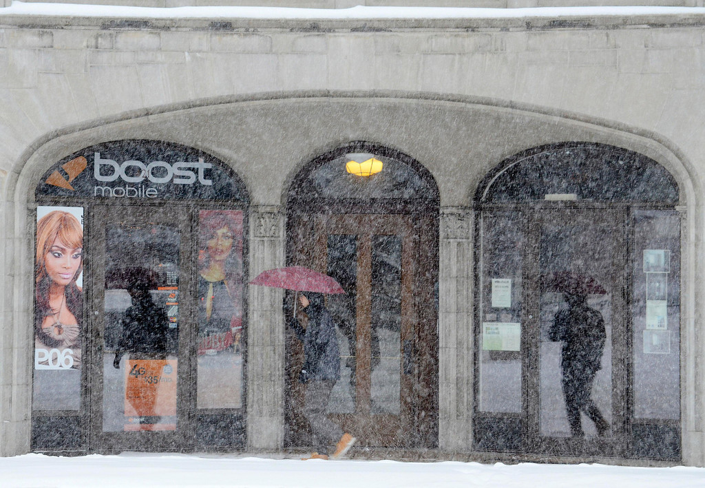 . A pedestrian passes a North Street storefront as snow falls in Pittsfield, Mass., Wednesday Feb 5, 2014. The storm is expected to drop a foot or more of snow on some areas of the state. (AP Photo/The Berkshire Eagle, Ben Garver)