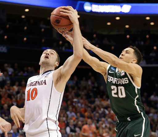 . Virginia\'s Mike Tobey (10) and Michigan State\'s Travis Trice (20) battle for a rebound during the first half of an NCAA tournament college basketball game in the Round of 32 in Charlotte, N.C., Sunday, March 22, 2015. (AP Photo/Nell Redmond)