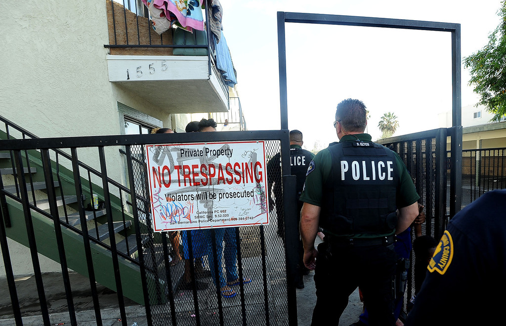 . Police enter the Evergreen Apartments along the 1500 block of Pumalo Street during a county wide police sweep in San Bernardino August 2, 2013. GABRIEL LUIS ACOSTA/STAFF PHOTOGRAPHER.