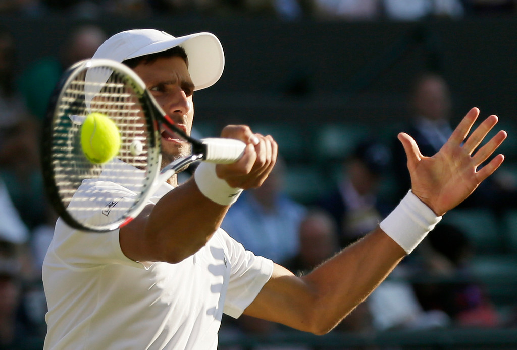 . Novak Djokovic of Serbia returns the ball to Tennys Sandgren of the US during their men\'s singles match on the second day at the Wimbledon Tennis Championships in London, Tuesday July 3, 2018. (AP Photo/Tim Ireland)