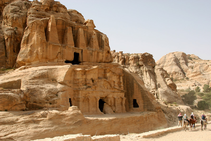 Petra - The 'Obelisk Tomb' and 'Bab as-Siq Triclinium' on the path from the park entrance to The Siq. The upper structure with the four pyramidal obelisks is a Nabataean tomb.  Underneath is a Nabataean triclinium (three-banked dining room) with it's three small chambers where annual feasts were held to commemorate the dead.