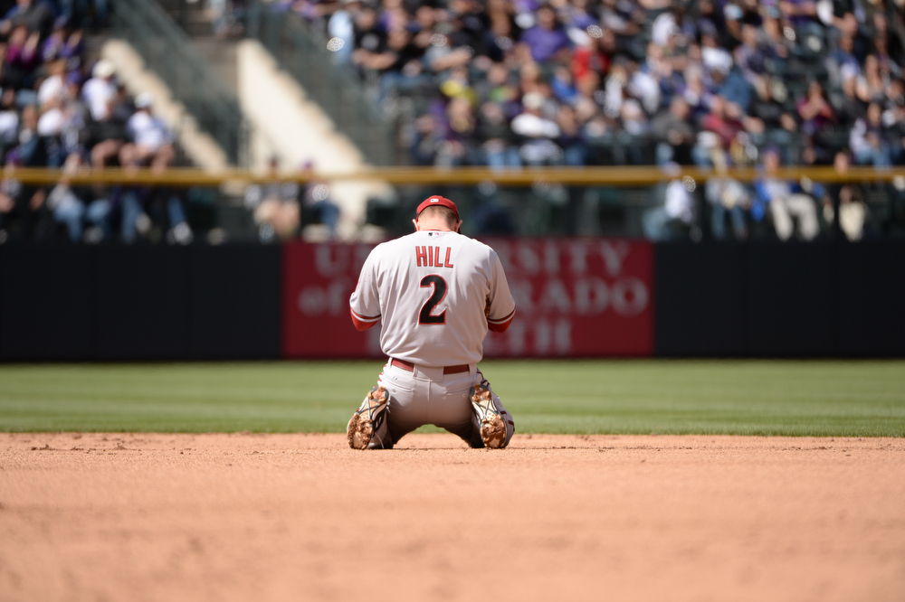 . DENVER, CO. - APRIL 4: The Diamondbacks\' Aaron Hill Hill (2) reacts after fumbling ball hit by the Rockies\' Michael Cuddyer (3) in the third inning. The Colorado Rockies hosted the Arizona Diamondbacks in the Rockies season home opener at Coors Field in Denver, Colorado Friday, April 4, 2014. (Photo by Hyoung Chang/The Denver Post)
