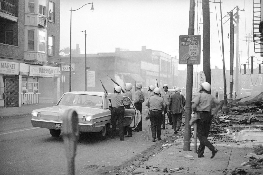 . Helmeted police officers look for a sniper believed to be in a building at an intersection in Cleveland?s troubled Hough area, July 19, 1966. This is the intersection where a black man was shot and killed tonight. Smoke drifts across the intersection from buildings burned in last night?s rioting. (AP Photo/Julian C. Wilson)