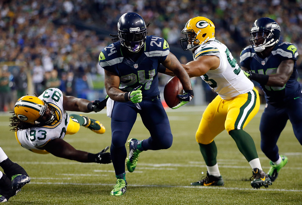 . SEATTLE, WA - SEPTEMBER 04: Running back Marshawn Lynch #24 of the Seattle Seahawks breaks the tackle of linebacker Nick Perry #53 of the Green Bay Packers as he scores a touchdown during the third quarter of the game at CenturyLink Field on September 4, 2014 in Seattle, Washington.  (Photo by Otto Greule Jr/Getty Images)