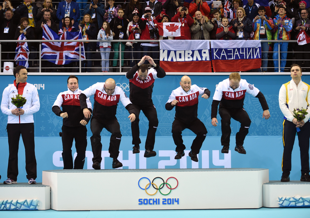 . (L-R) Canada\'s gold medallists Caleb Flaxey, Ryan Harnden, E.J. Harnden, Ryan Fry and Brad Jacobs jump on the podium during the Men\'s Curling Flower Ceremony at the Ice Cube Curling Center in Sochi during the Sochi Winter Olympics on February 21, 2014. LEON NEAL/AFP/Getty Images