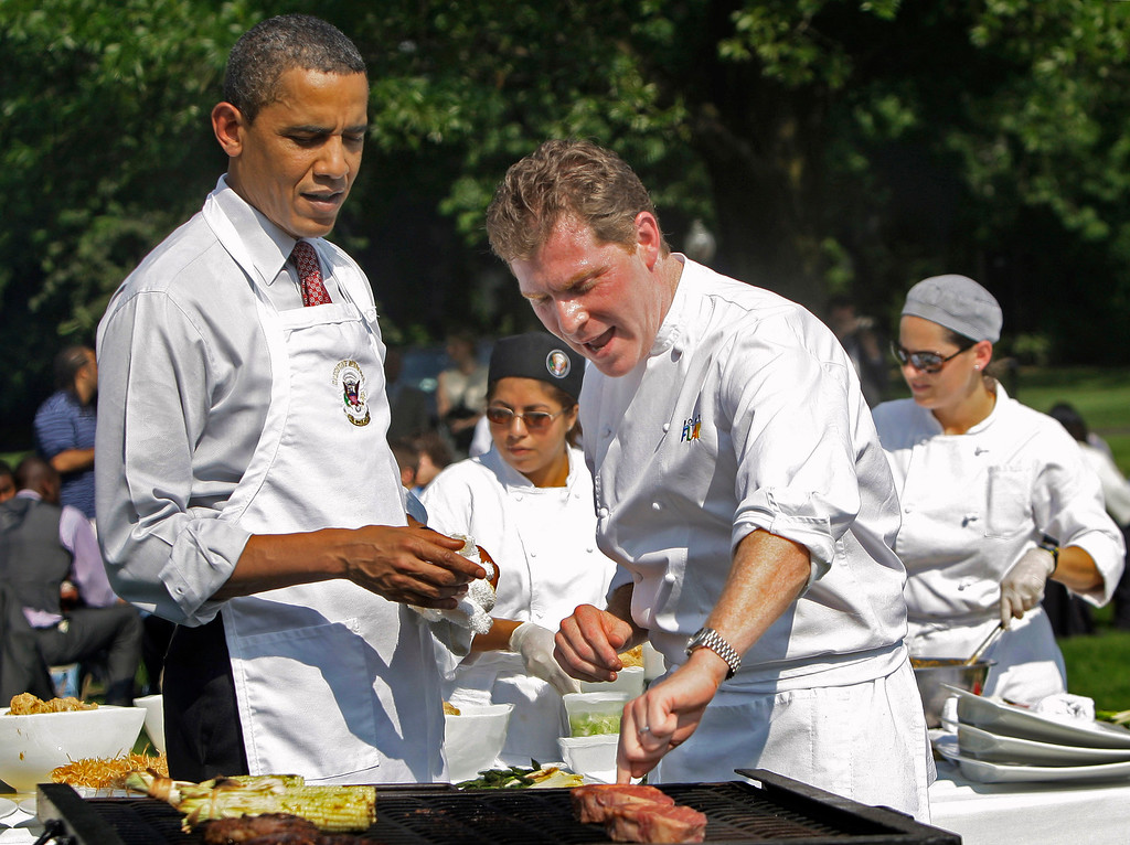 """. In this June 19, 2009, file photo President Barack Obama gets grilling tips from White Houses guest chef Bobby Flay on the South Lawn of the White House in Washington. Flay said it was \""""probably my greatest professional moment,\"""" and described Obama: \""""Thirty seconds into it he made me feel like he and I had known each other for a long time.\"""" (AP Photo/Haraz N. Ghanbari, File)"""
