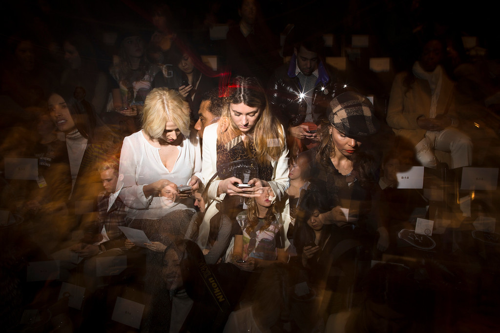 . In this Feb. 7, 2013 photo made with multiple flash exposures, spectators pour over their cell phones while they wait for a show to begin at the Mercedes-Benz Fashion Week tents at Lincoln Center, in New York. (AP Photo/John Minchillo)