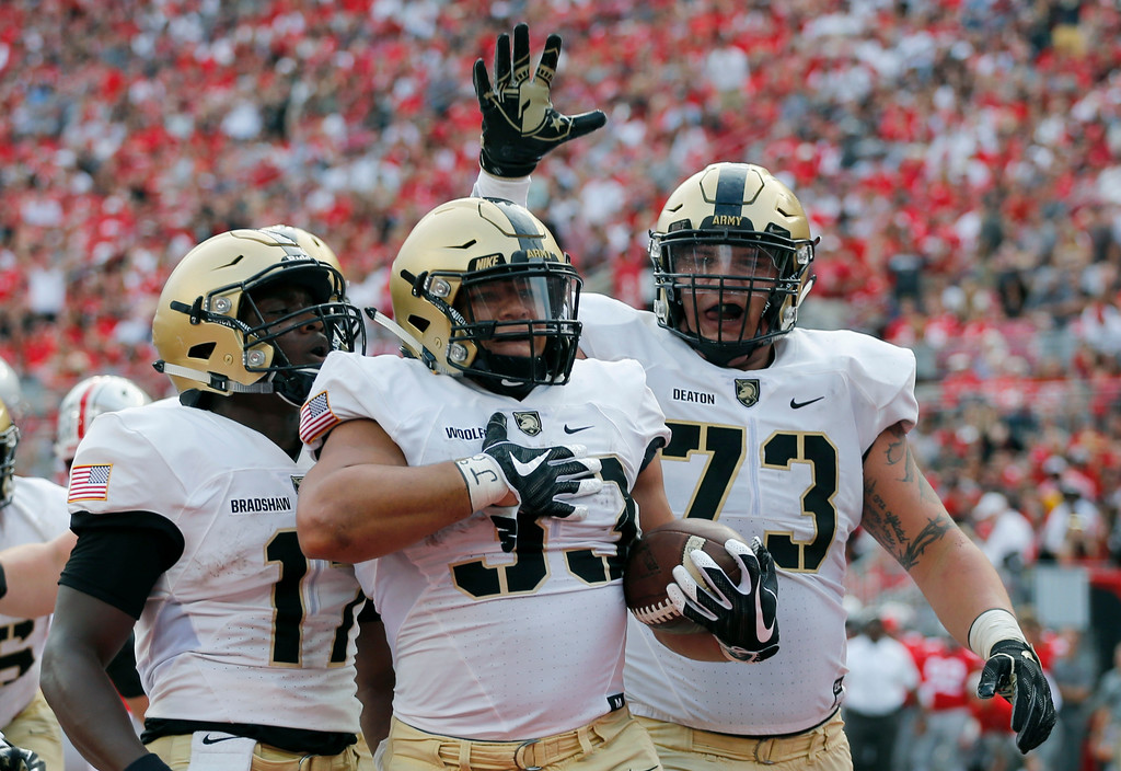 . Army running back Darnell Woolfolk, center, celebrates his touchdown against Ohio State with teammates Ahmad Bradshaw, left, and Jaxson Deaton during the first half of an NCAA college football game Saturday, Sept. 16, 2017, in Columbus, Ohio. (AP Photo/Jay LaPrete)