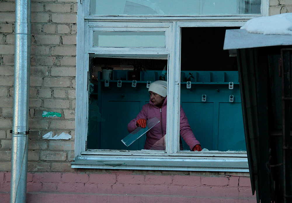 Description of . In this photo provided by Chelyabinsk.ru a woman cleans away glass debris from a window after a meteorite explosion over Chelyabinsk region on Friday, Feb. 15, 2013. A meteor exploded in the sky above Russia on Friday, causing a shockwave that blew out windows injuring hundreds of people and sending fragments falling to the ground in the Ural Mountains.  The Russian Academy of Sciences said in a statement hours after the Friday morning fall that the meteor entered the Earth's atmosphere at a speed of at least 54,000 kph (33,000 mph) and shattered about 30-50 kilometers (18-32 miles) above ground. The fall caused explosions that broke glass over a wide area. (AP Photo/ Yevgenia Yemelyanova, Chelyabinsk.ru)