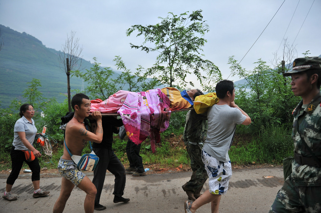 . Villagers carry an injured woman in the quake-hit area on August 4, 2014 in Zhaotong, China. A 6.5-magnitude earthquake hit Zhaotong\'s Ludian county on August 3, killing at least 410 people.  (Photo by ChinaFotoPress/ChinaFotoPress via Getty Images)