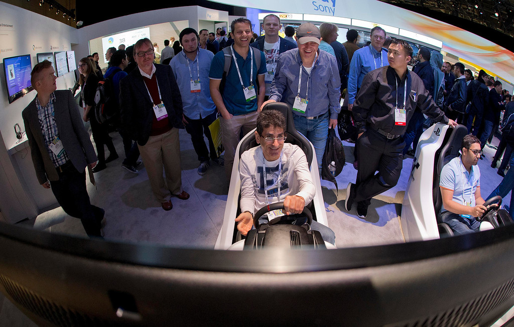 . Trade show attendees play with the Sony PlayStation Gran Turismo driving simulator at the International Consumer Electronics Show, Wednesday, Jan. 8, 2014, in Las Vegas. (AP Photo/Julie Jacobson)