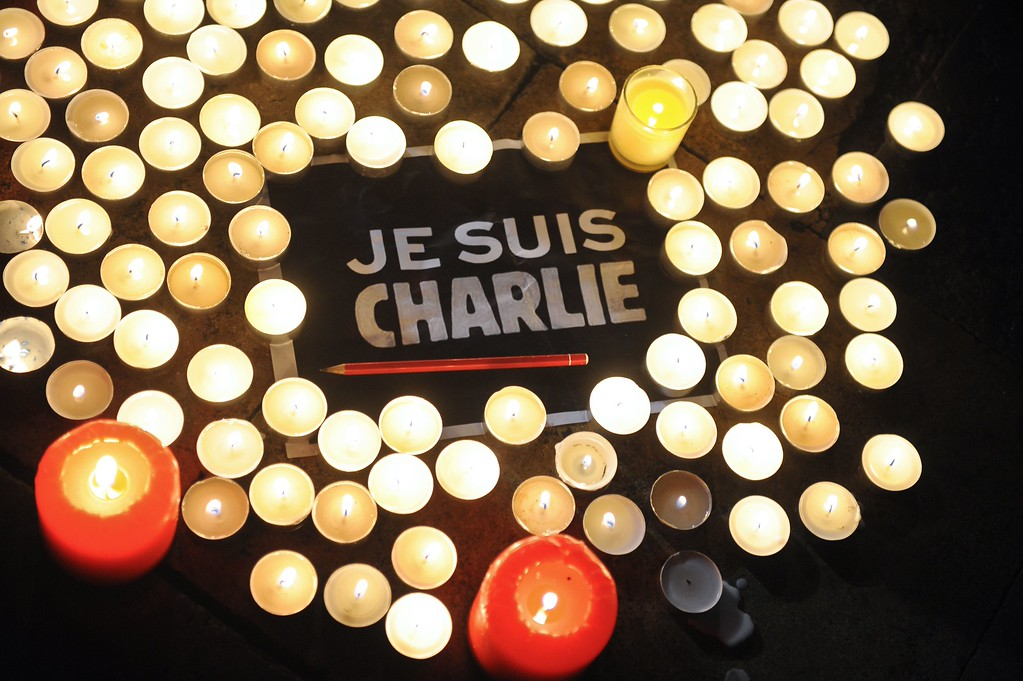 . Candles are placed next to a sign reading \'Je suis Charlie\' (I am Charlie) and a pen in La Rochelle on January 7, 2015, as people gathered to pay tribute to the twelve people killed in an attack by two armed gunmen on the offices of French satirical newspaper Charlie Hebdo in Paris. A stunned and outraged France was in mourning on January 8, as security forces desperately hunted two brothers suspected of gunning down 12 people in an Islamist attack on a satirical weekly.   AFP PHOTO / XAVIER LEOTY/AFP/Getty Images