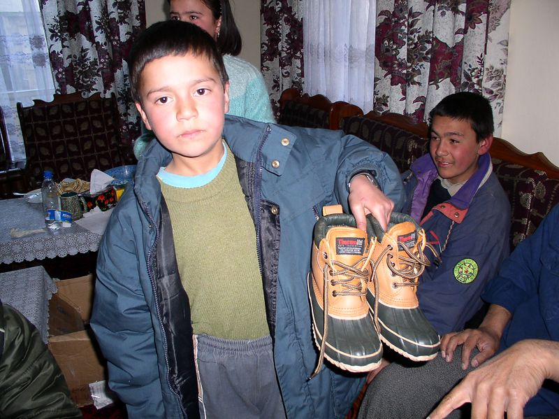Story behind this one is: Ahmed (Pashtoon's son) originally picked these, however, when the other kids started coming in, he gave them up eagerly so this boy got a good pair of boots. He gave the soups to the kids above. The boy sitting behind him on the couch is his brother (18 years old) and head of the household. He is a shopkeeper and sells gum, matches, and other small items. He receives his stock from an uncle. He supports an entire family by this effort.