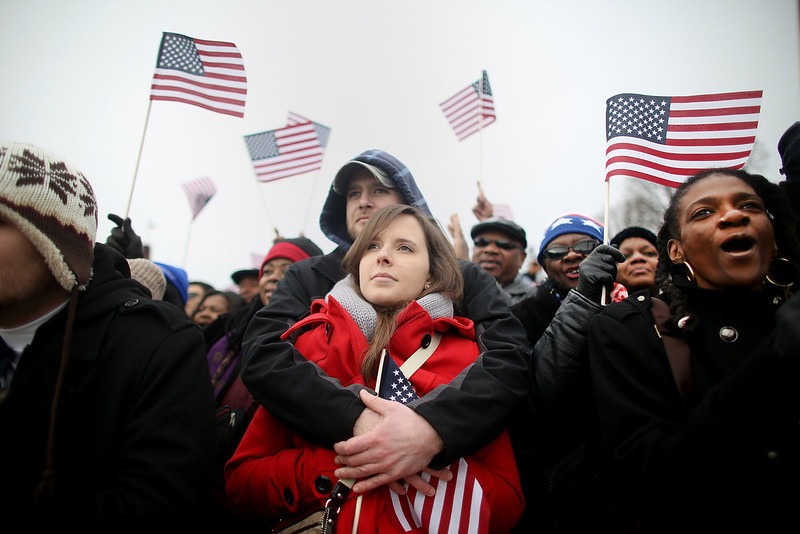 . Steven Healey and Amanda Young, center, embrace as Toia Littlefield, right, watches near the U.S. Capitol building on the National Mall while attending the public Inauguration ceremony on January 21, 2013 in Washington, DC. U.S. President Barack Obama was ceremonially sworn in for his second term today.  (Photo by Mario Tama/Getty Images)