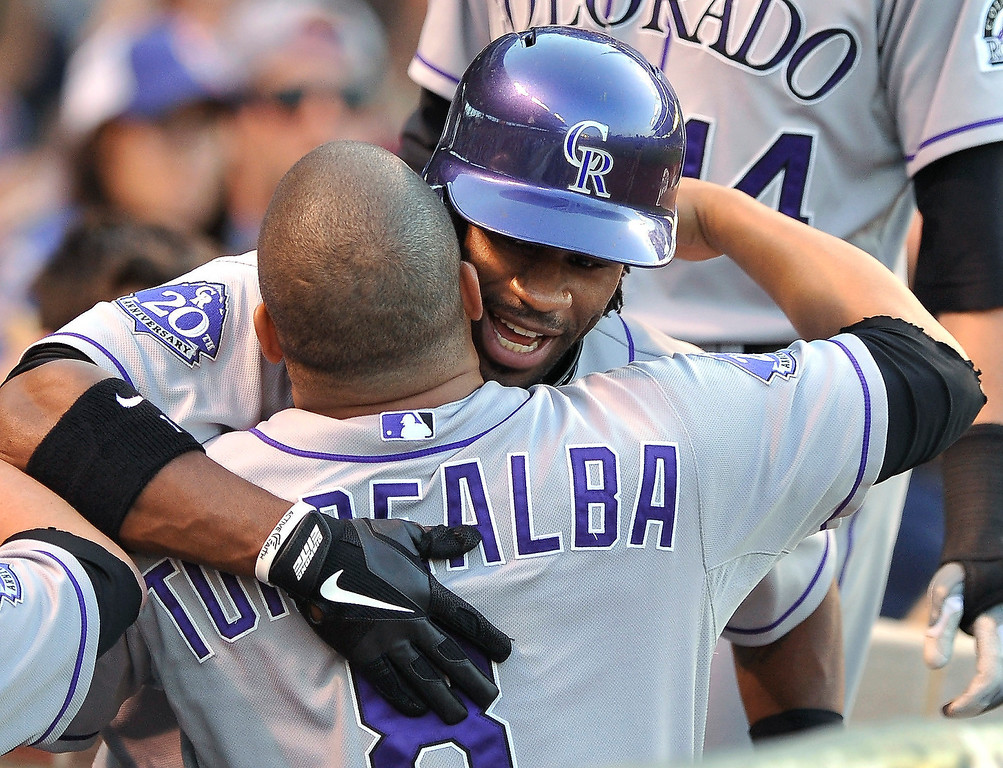 . Colorado Rockies\' Eric Young Jr. back, celebrates with Yorvit Torrealba (8) after hitting a two-run home run against the Chicago Cubs during the second inning of a baseball game in Chicago, Tuesday, May 14, 2013. (AP Photo/Paul Beaty)