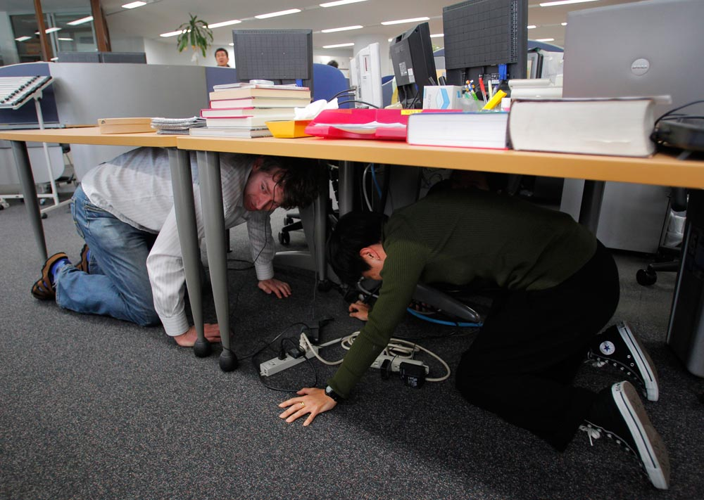 . Reporters at the Associated Press Tokyo Bureau in Tokyo take shelter under a table while a strong earthquake strikes eastern Japan Friday afternoon, March 11, 2011. (AP Photo/Itsuo Inouye)