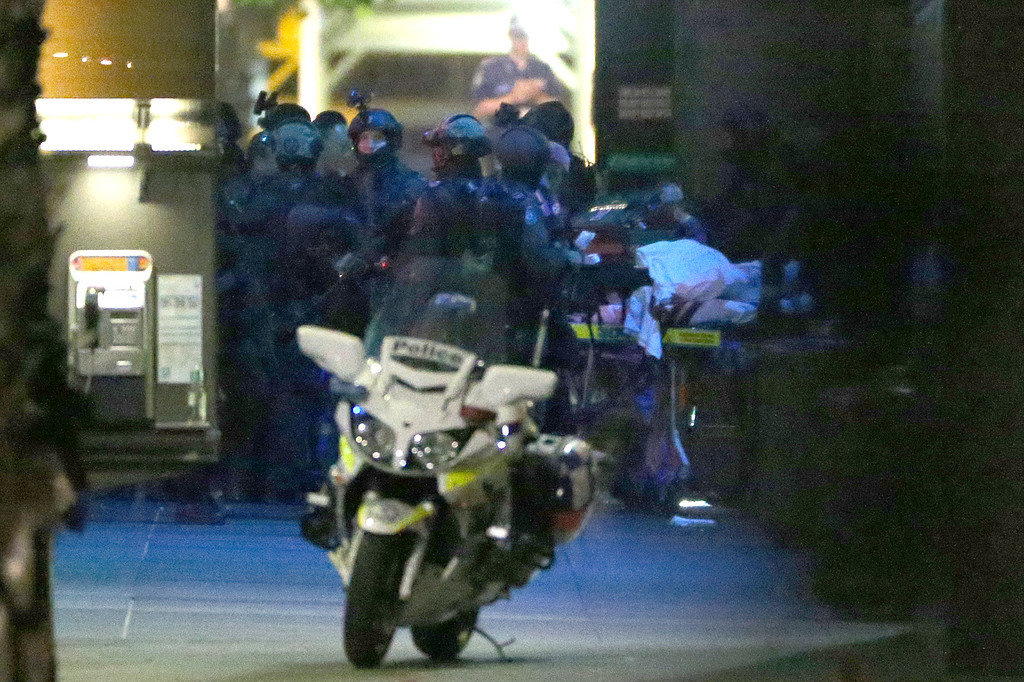 ". Armed tactical response officers stand by as a stretcher is wheeled past after a siege in the central business district of Sydney , Australia, Tuesday, Dec. 16, 2014.  A swarm of heavily armed police stormed the cafe in the heart of downtown Sydney early Tuesday, ending a siege where a gunman had been holding an unknown number of people hostage for more than 16 hours. A police spokesman confirmed ""the operation is over,\"" but would not release any further details about the fate of the gunman or his remaining captives. After a flurry of loud bangs, police swooped into the Lindt Chocolat Cafe shortly after five or six hostages were seen running from the building. (AP Photo/Glenn Nicholls)"