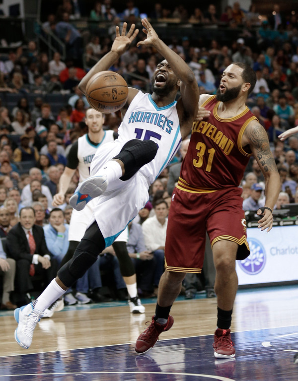 . Charlotte Hornets\' Kemba Walker (15) is fouled as he drives against Cleveland Cavaliers\' Deron Williams (31) during the first half of an NBA basketball game in Charlotte, N.C., Friday, March 24, 2017. (AP Photo/Chuck Burton)