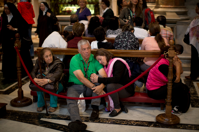 . Worshipers rest inside St. Peter\'s Basilica at the Vatican, Saturday, April 26, 2014. Pilgrims and faithful are gathering in Rome to attend Sunday\'s ceremony at the Vatican where Pope Francis will elevate in a solemn ceremony John XXIII and John Paul II to sainthood. (AP Photo/Emilio Morenatti)