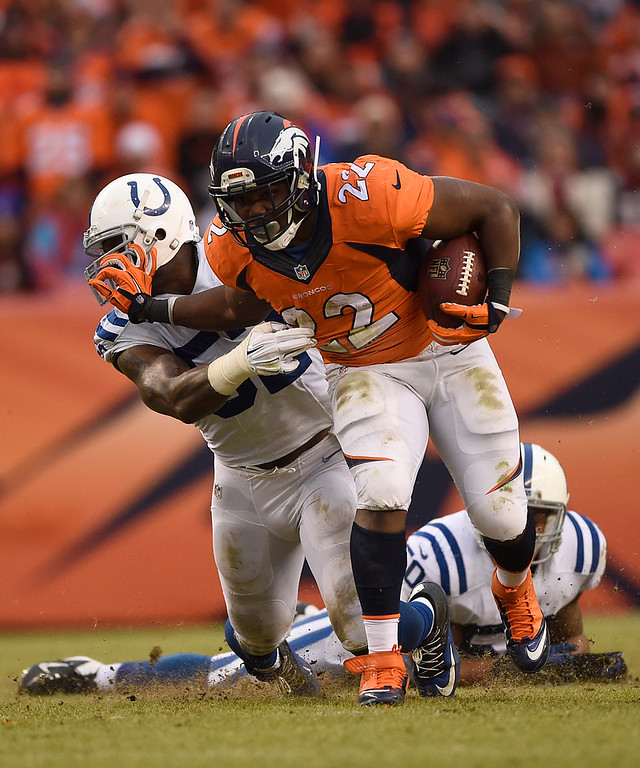 . C.J. Anderson (22) of the Denver Broncos stiff-arms Colt Anderson (32) of the Indianapolis Colts on a run in the second quarter. The Denver Broncos played the Indianapolis Colts in an AFC divisional playoff game at Sports Authority Field at Mile High in Denver on January 11, 2015. (Photo by AAron Ontiveroz/The Denver Post)