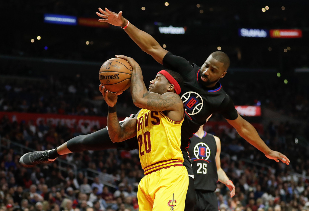 . Cleveland Cavaliers\' Kay Felder, center, is fouled by Los Angeles Clippers\' Raymond Felton during the second half of an NBA basketball game Saturday, March 18, 2017, in Los Angeles. (AP Photo/Jae C. Hong)