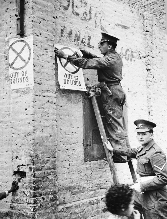 ". British Military Police affix ""Out of bounds\"" posters to the walls in the Arab section of Ismalia, Egypt, March 20, 1952. The British Army is pulling out of the area after clearing it of terrorists and having many battles between Egyptian police and British troops. (AP Photo)"