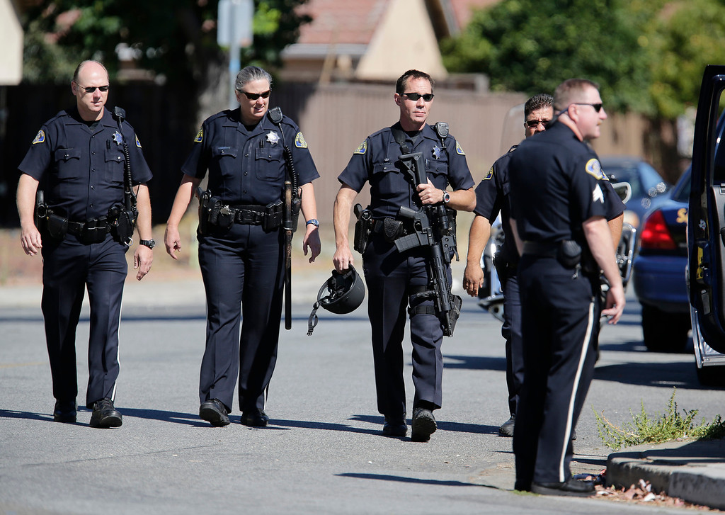 . Members of the San Jose Police Depart walk down Diana Lane near Story Rd. as they search the neighborhood for a gunman who tried to rob a check-cashing store in East San Jose, Calif. on Thursday, Aug. 1, 2013.  (Gary Reyes/Bay Area News Group)