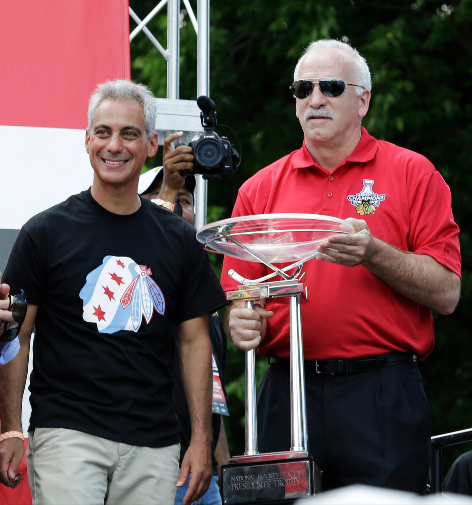 . Chicago Blackhawks head coach Joel Quenneville, right, holds the NHL\'s Presidents Cup with Chicago Mayor Rahm Emanuel looking on during a rally in Grant Park to honor the NHL Stanley Cup hockey champions Friday, June 28, 2013, in Chicago. (AP Photo/Nam Y. Huh)
