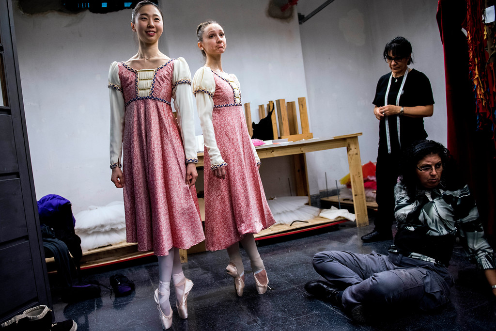 . In this Wednesday, Sept. 6, 2017 photo, ballet dancers Eunsil Kim, left, and Paula Penachio try on their dresses at the costume workshop at the Adela Reta Auditorium in Montevideo, Uruguay. The building also has a carpentry workshop where the set designs are built for performances, which now often sell out. (AP Photo/Matilde Campodonico)