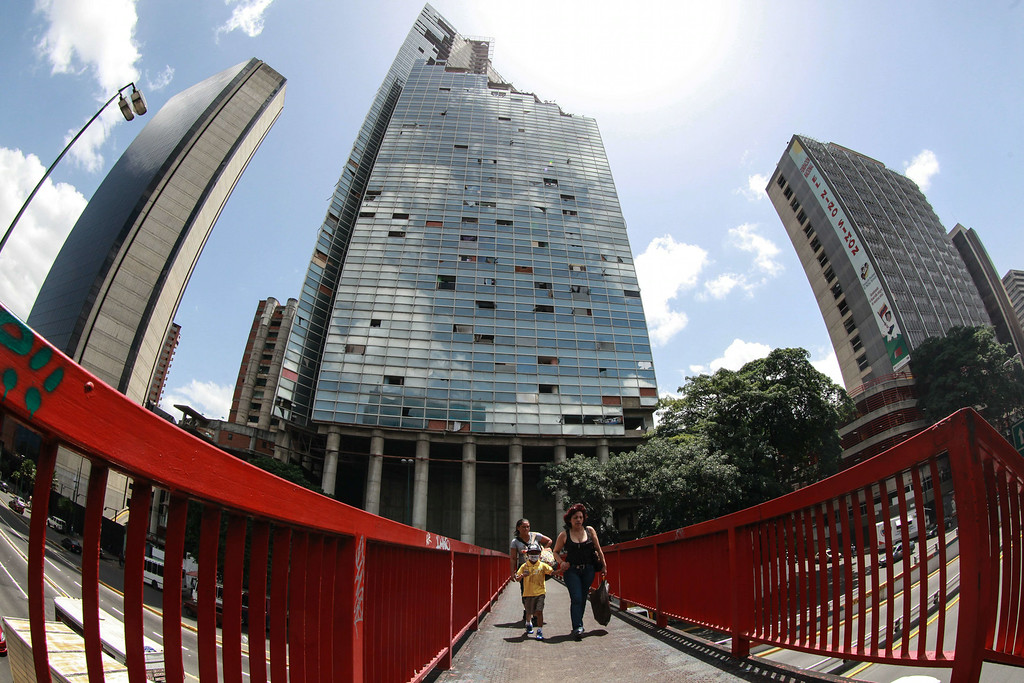 . People voluntarily leave the Tower of David, an abandoned skyscraper in Caracas originally intended to be an office building that became a \'vertical slum\', during its eviction on July 22, 2014. The government began the eviction and relocation of hundreds of families that were illegally occupying the building. FEDERICO PARRA/AFP/Getty Images