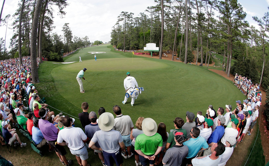 . Matt Kuchar putts on the 10th green during the fourth round of the Masters golf tournament Sunday, April 13, 2014, in Augusta, Ga. (AP Photo/Charlie Riedel)