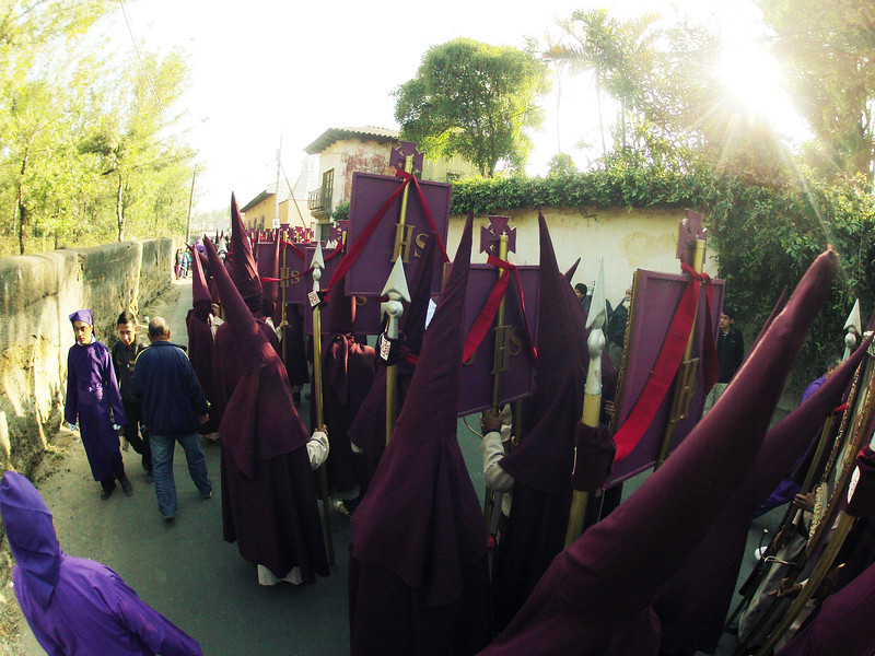 A procession slowly moves past my house in Antigua, Guatemala on March 15, 2013. Purple robes with purple hoods are good. The whites ones are more worrisome. Suposedly, those guys who used to wear the white robes got the idea from these guys that wear purple robes. Don't quote me on that though. Photo by Scott Umstattd
