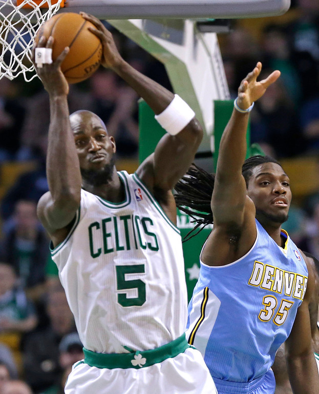 . Boston Celtics power forward Kevin Garnett (5) brings down a rebound against Denver Nuggets small forward Kenneth Faried (35) during the first half of an NBA basketball game in Boston, Sunday, Feb. 10, 2013. (AP Photo/Elise Amendola)