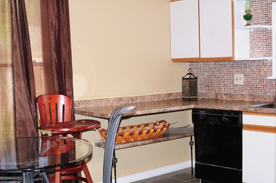 The second-floor kitchen has ample cupboard and under-counter storage space. Decorative copper-colored tiles adorn the wall above the counter top. (High chair, glass table and chairs not included.)